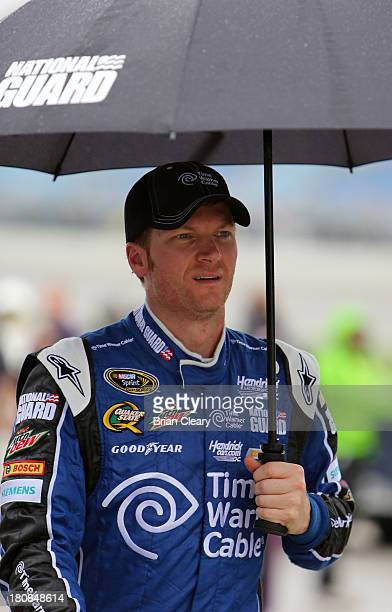Dale Earnhardt Jr driver of the Time Warner Cable Chevrolet walks on pit road during a rain delay for the NASCAR Sprint Cup Series Geico 400 at...