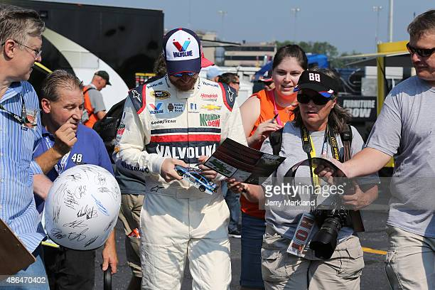 Dale Earnhardt Jr driver of the Valvoline Chevrolet signs autographs for fans during practice for the NASCAR Sprint Cup Series Bojangles' Southern...