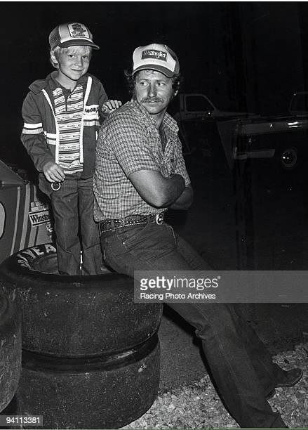 Dale Earnhardt Jr gives the camera a smile while his father is distracted