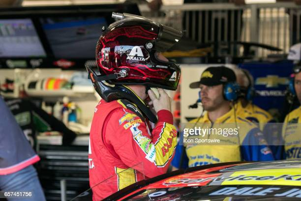 Dale Earnhardt Jr puts his helmet on and prepares to get in his car during practice for the Auto Club 400 NASCAR Monster Energy Cup Series race on...