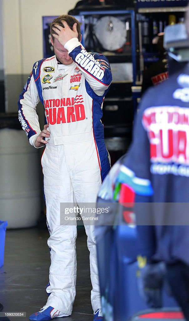 Dale Earnhardt, Jr., stands in his garage after causing a 12-car pile-up during test trials at Daytona International Speedway in Daytona Beach, Florida, Friday, January 11, 2013.