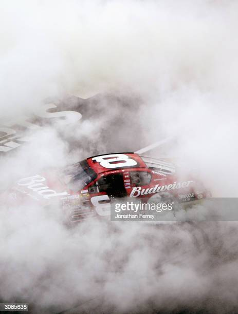 Dale Earnhardt Jr.'s Budweiser Chevrolet emerges from the smoke after doing victorious donuts after winning during the NASCAR Nextel Cup Golden...