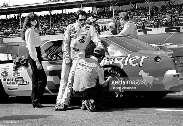 Dale Earnhardt Sr and his wife Teresa Earnhardt stand beside the Wrangler Ford Thunderbird as a crew member checks the tire pressure prior to the...