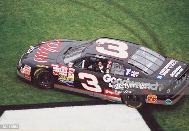 Dale Earnhardt Sr driver of the GM Goodwrench Chevrolet celebrates in the infield grass after winning the 1998 NASCAR Winston Cup Daytona 500 at the...