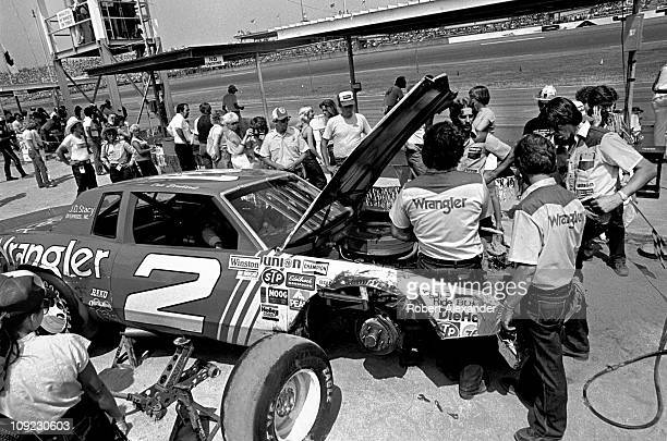 Dale Earnhardt Sr driver of the Wrangler Pontiac Grand Prix sits in his car while it is repaired after an accident during the 1981 Firecracker 400 at...
