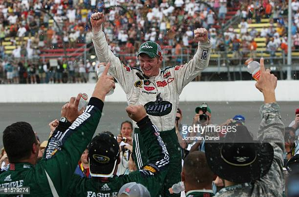 Dale EarnhardtJr celebrates with his crew in victory lane after winning the NASCAR Sprint Cup Series Lifelock 400 at the Michigan International...