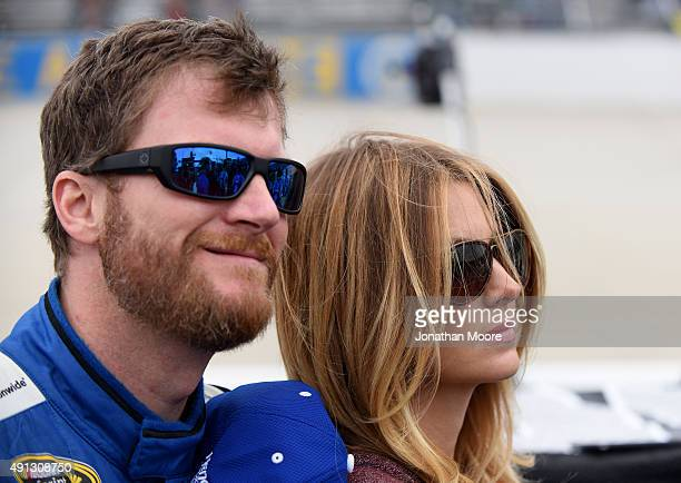 Dale Earnrhardt Jr driver of the Nationwide Plenti Chevrolet and fiance Amy Reimann stand on the grid before NASCAR Sprint Cup Series AAA 400 at...