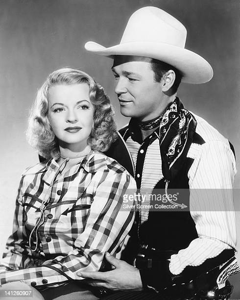 Dale Evans , US actress and singer, wearing a plaid shirt, and her husband, Roy Rogers , US actor and singer, wearing a white cowboy hat, neckerchief...