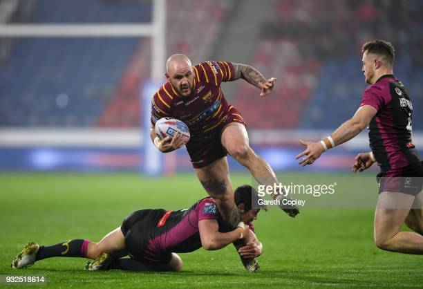 Dale Ferguson of Huddersfield Giants is tackled by Danny McGuire of Hull KR during the Betfred Super League match between Huddersfield Giants and...