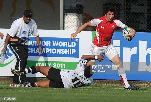 Dale Ford of Wales is tackled by Teti Tela of Fiji during the IRB Junior World Championship match between Wales and Fiji at Plebiscito Stadium on...