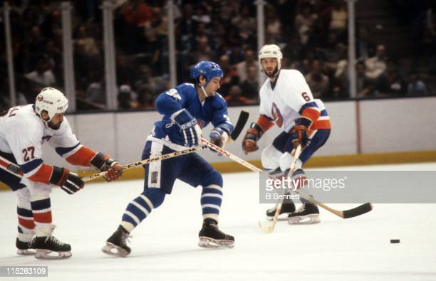 Dale Hunter of the Quebec Nordiques skates with the puck as Ken Morrow and John Tonelli of the New York Islanders defend during an Eastern Conference...