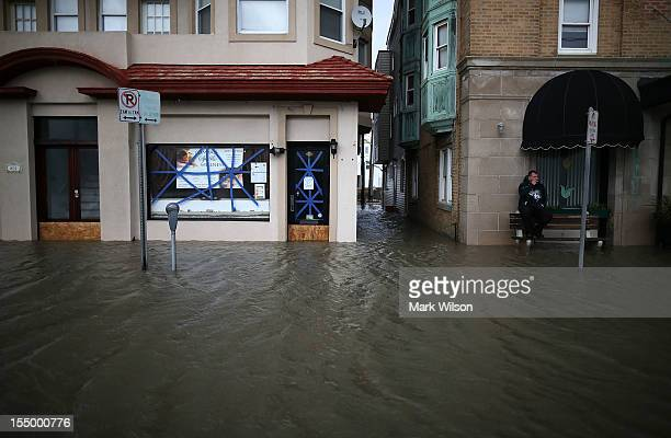 Dale Kelly sits on a bench on a flooded street October 30 2012 in Ocean City New Jersey Hurricane Sandy made landfall last night on the New Jersey...