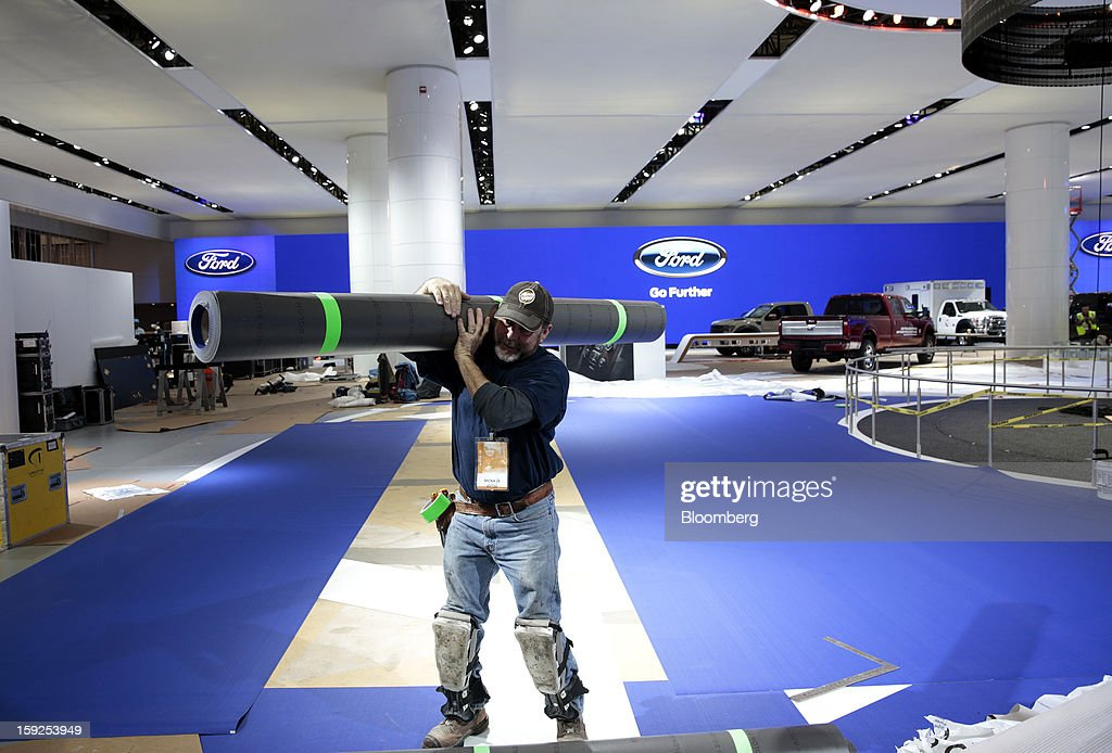 Dale Mills carries flooring at the Ford Motor Co. exhibit during an advance tour of the North American International Auto Show (NAIAS) at Cobo Hall in Detroit, Michigan, U.S., on Thursday, Jan. 10, 2013. More than 23,000 attendees representing almost 2,000 companies are expected to attend the industry preview for NAIAS on Jan. 16-17. The general public can attend the show from Jan. 19-27. Photographer: Jeff Kowalsky/Bloomberg via Getty Images