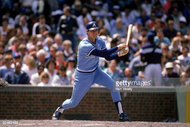 Dale Murphy of the Atlanta Braves follows through on his swing during a game against the Chicago Cubs in 1986 at Wrigley Field in Chicago Illinois...