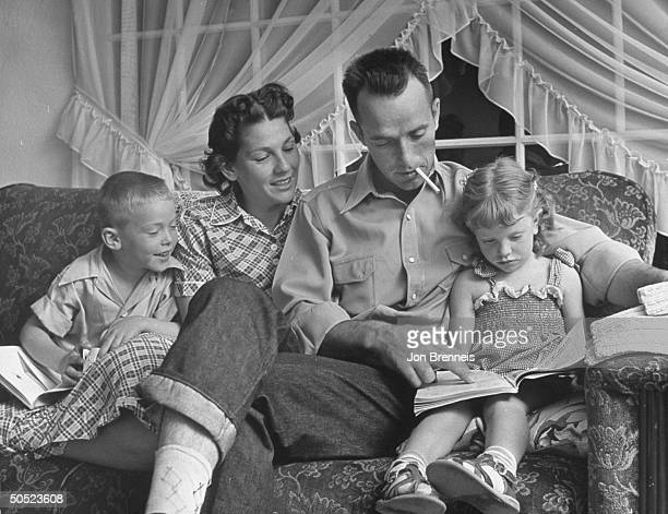 Dale Sprout and his family looking at a book in family living room