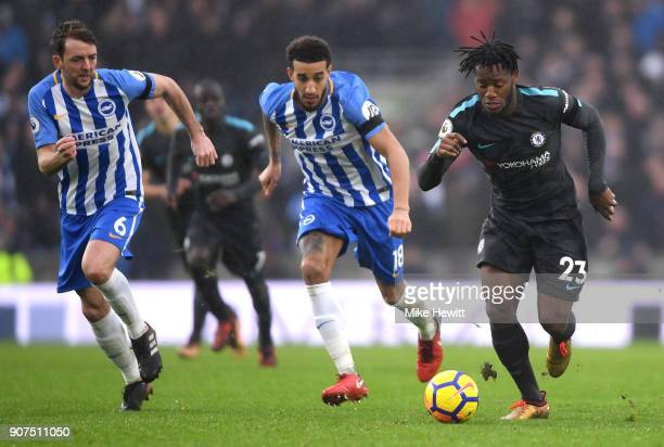 Dale Stephens and Connor Goldson of Brighton and Hove Albion chase down Michy Batshuayi of Chelsea during the Premier League match between Brighton...