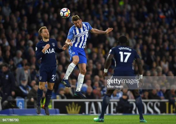 Dale Stephens of Brighton and Hove Albion heads the ball as Christian Eriksen of Tottenham Hotspur looks on during the Premier League match between...