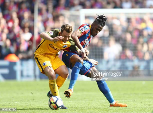 Dale Stephens of Brighton and Hove Albion is challenged by Wilfried Zaha of Crystal Palace during the Premier League match between Crystal Palace and...