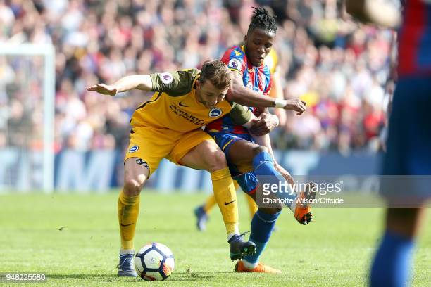 Dale Stephens of Brighton and Wilfried Zaha of Crystal Palace battle for the ball during the Premier League match between Crystal Palace and Brighton...