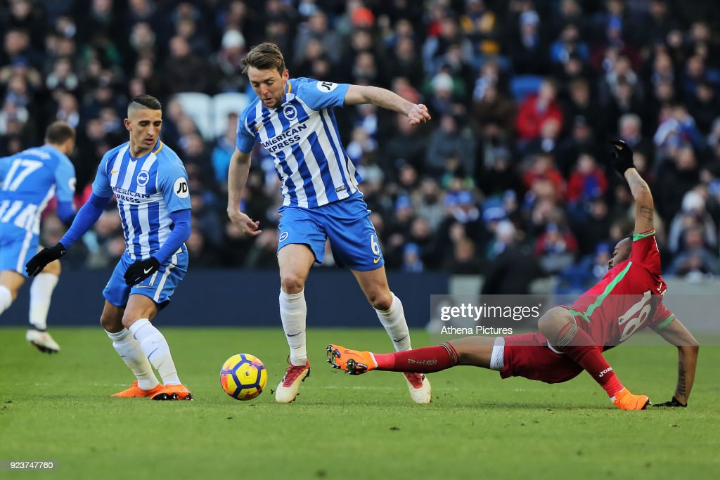 Dale Stephens of Brighton (C) tackled by Jordan Ayew of Swansea City (R) during the Premier League match between Brighton and Hove Albion and Swansea City and at the Amex Stadium on February 24, 2018 in Brighton, England.