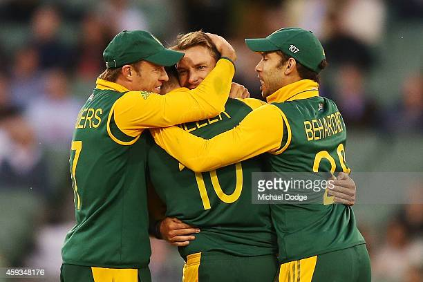 Dale Steyn of South Africa is hugged by teamates as they celebrate the wicket of George Bailey of Australia during game four of the One Day...