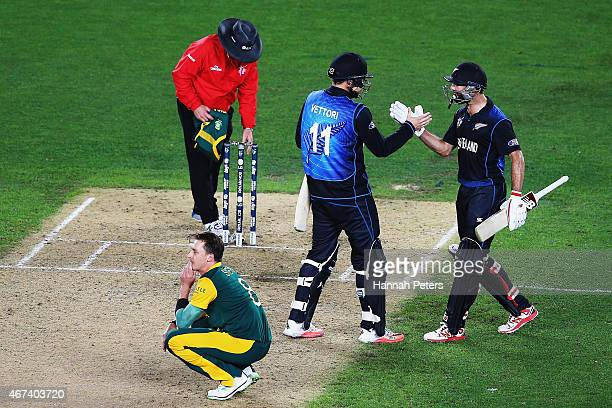 Dale Steyn of South Africa looks on as Daniel Vettori of New Zealand and Grant Elliott of New Zealand celebrate winning the 2015 Cricket World Cup...
