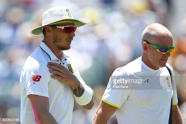 Dale Steyn of South Africa walks from the field with the team physio after injuring his shoulder during day two of the First Test match between...