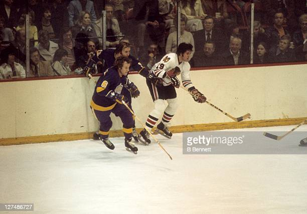 Dale Tallon of the Chicago Blackhawks and Sheldon Kannegiesser of the Los Angeles Kings skate on the ice during their game in 1975 at the Chicago...