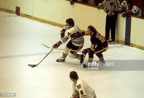Dale Tallon of the Chicago Blackhawks skates with the puck as Don Kozak of the Los Angeles Kings defends during their game in 1975 at the Chicago...