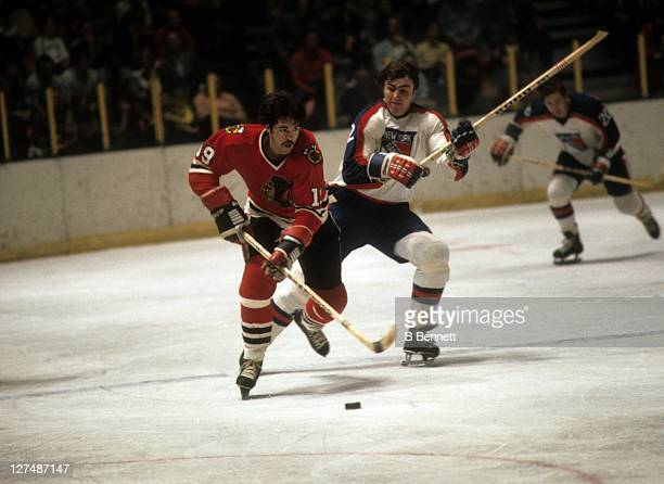 Dale Tallon of the Chicago Blackhawks skates with the puck as Nick Fotiu of the New York Rangers defends during their game circa 1976 at the Madison...