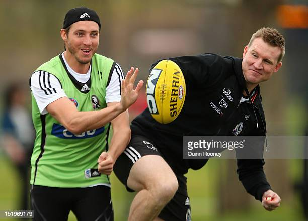 Dale Thomas and Nathan Buckley the coach of the Magpies contest for the ball during a Collingwood Magpies AFL training session at Gosch's Paddock on...