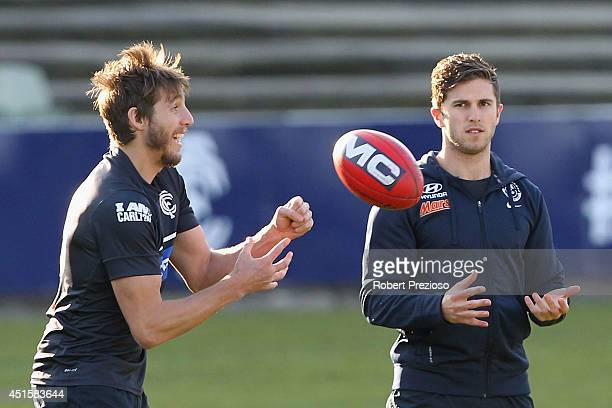 Dale Thomas handballs as Marc Murphy looks on during a Carlton Blues AFL training session at Visy Park on July 2 2014 in Melbourne Australia