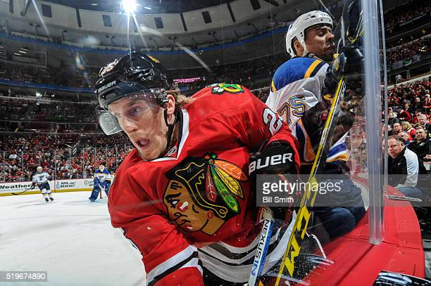 Dale Weise of the Chicago Blackhawks and Ryan Reaves of the St. Louis Blues get physical by the boards in the first period of the NHL game at the...