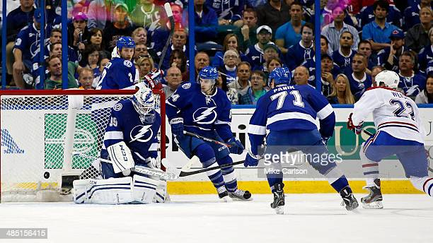 Dale Weise of the Montreal Canadiens scores the overtime winning goal past goalie Anders Lindback of the Tampa Bay Lightning as defenders Eric Brewer...