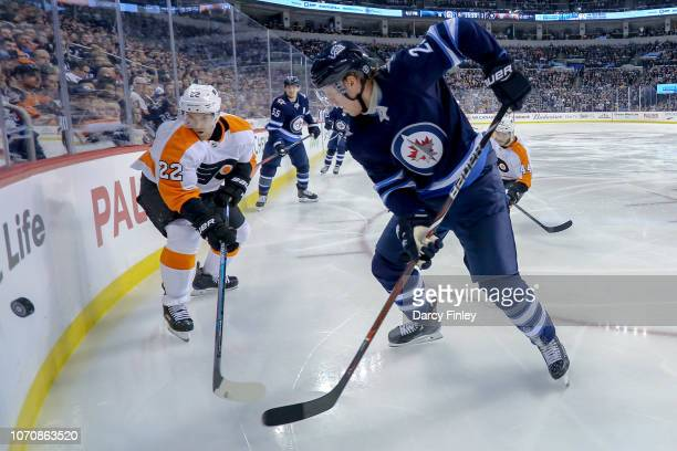 Dale Weise of the Philadelphia Flyers and Patrik Laine of the Winnipeg Jets battle for the puck along the corner boards during third period action at...