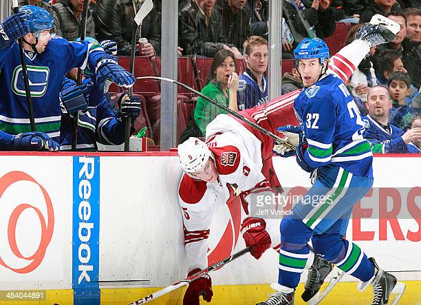 Dale Weise of the Vancouver Canucks checks Connor Murphy of the Phoenix Coyotes near the Vancouver bench during their NHL game at Rogers Arena on...