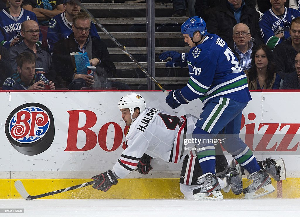 Dale Weise #32 of the Vancouver Canucks checks Niklas Hjalmarsson #4 of the Chicago Blackhawks during their NHL game at Rogers Arena February 1, 2013 in Vancouver, British Columbia, Canada. Vancouver won 2-1 in a shootout.