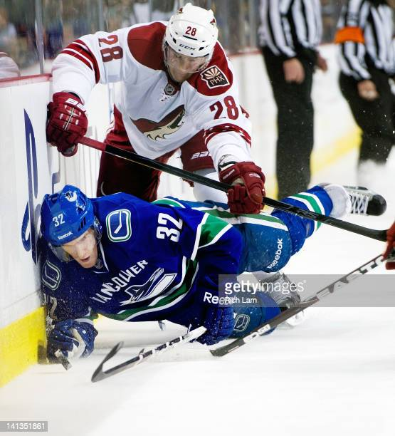 Dale Weise of the Vancouver Canucks is knocked down to the ice by Lauri Korpikoski of the Phoenix Coyotes during the second period in NHL action on...