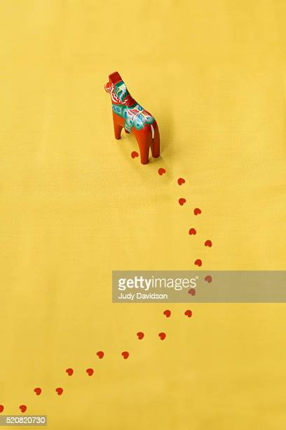 Dalecarlian red Swedish horse with a trail of hoof prints on a plain yellow background