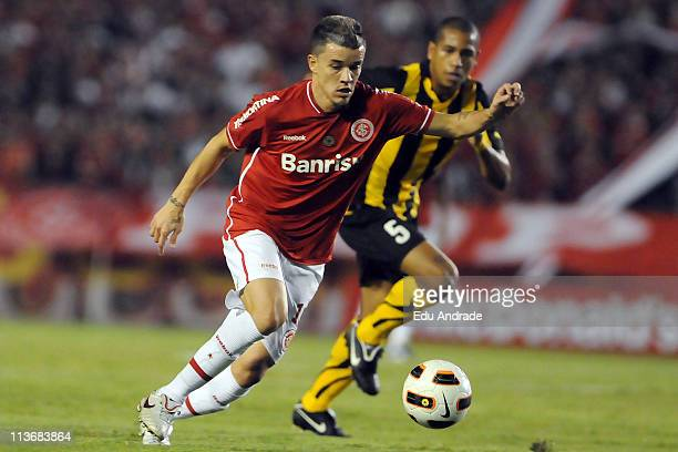 DAlessandro of Internacional struggles for the ball with Freitas of Penarol during a match as part of the Copa Santander Libertadores 2011 at Beira...