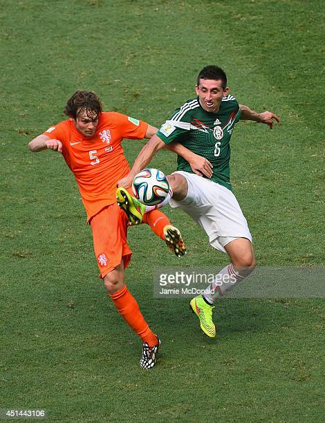 Daley Blind of the Netherlands and Hector Herrera of Mexico compete for the ball during the 2014 FIFA World Cup Brazil Round of 16 match between...
