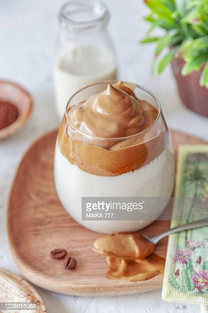 dalgona coffee, a trendy fluffy creamy whipped coffee, in a glass on a rustic white background and coffee beans spread around - dalgona stock pictures, royalty-free photos & images