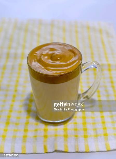 dalgona coffee in a clear glass mug- a trendy drink - dalgona stock pictures, royalty-free photos & images