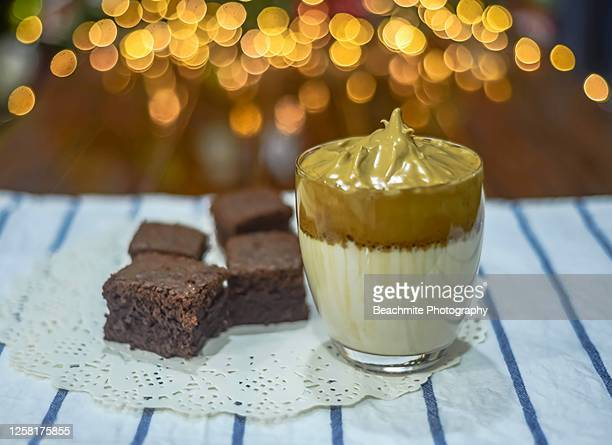 dalgona coffee in a glass and brownies with defocused lights background - trendy drink - dalgona stock pictures, royalty-free photos & images