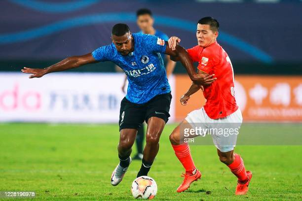 Dalian Pro's Jose Salomon Rondon fights for the ball with Guangzhou Everygrande's Huang Bowen during their Chinese Super League football match in...