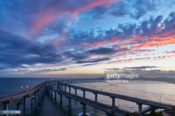 dalian xinghai bay bridge in the sunset glow. - dalian stock photos and pictures