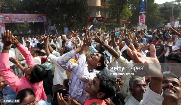 Dalit followers try to catch flowers which were showered from the helicopter on the 51st Death Anniversary of Dr Ambedkar at Chaityabhoomi Mumbai