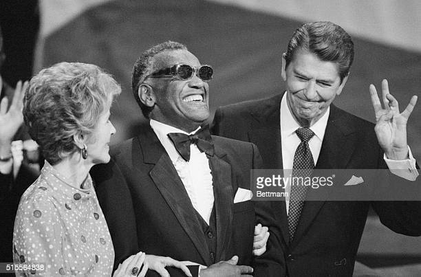 A smiling Ray Charles joins President Ronald Reagan and First Lady Nancy Reagan on the podium taking in the applause after Charles sang America the...
