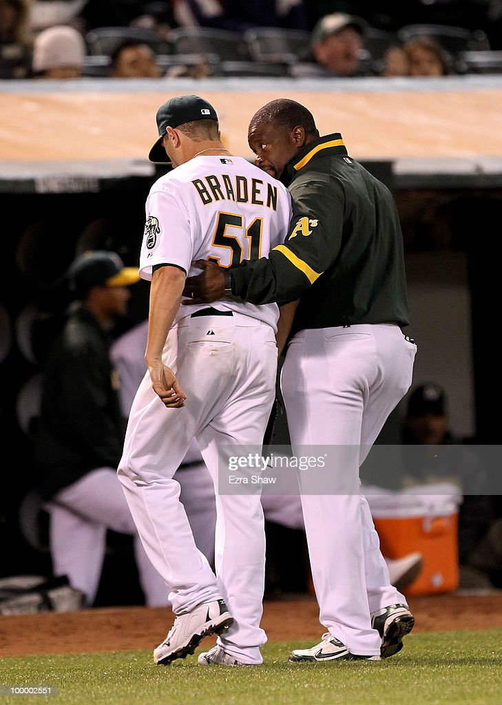 Dallas Braden #51 of the Oakland Athletics leaves the field with the trainer after getting injured in the seventh inning of their game against the Detroit Tigers at the Oakland-Alameda County Coliseum on May 19, 2010 in Oakland, California. Braden injured himself on the play and was taken out of the game.
