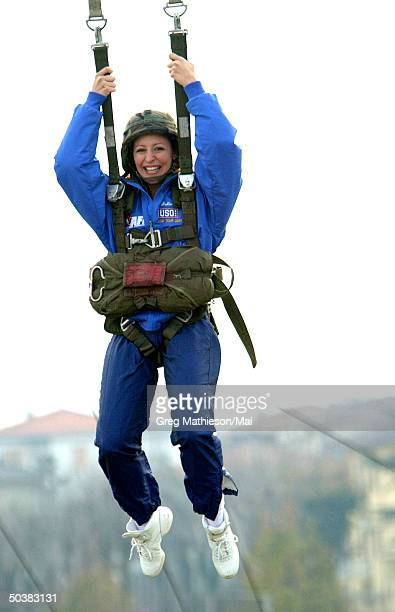 A Dallas Cowboy Cheerleader hanging from a parachute harness after jumping off a 5 story practice jump tower as part of the USO Holiday Tour